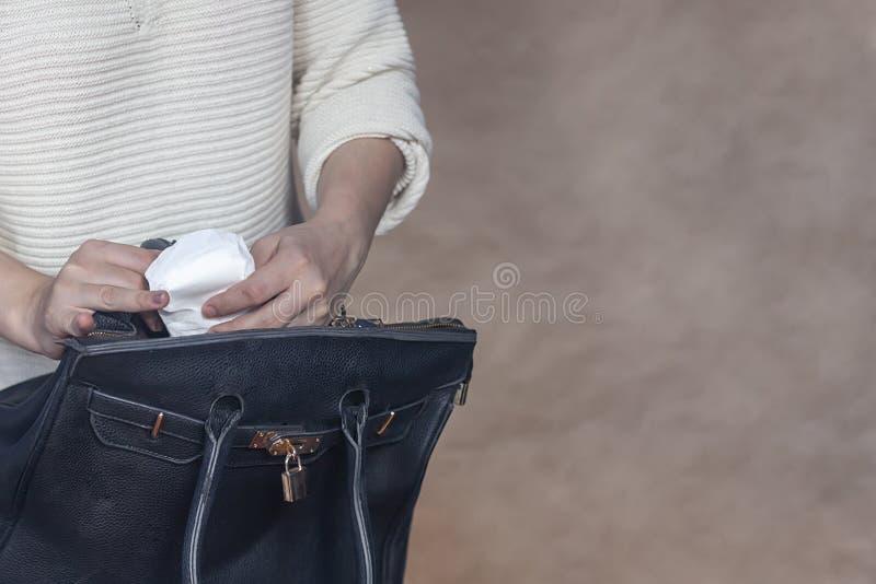 Le donne tengono un cuscinetto mestruale Giovane donna che elimina un cuscinetto sanitario dalla sua borsa Cuscinetto mestruale b fotografia stock libera da diritti