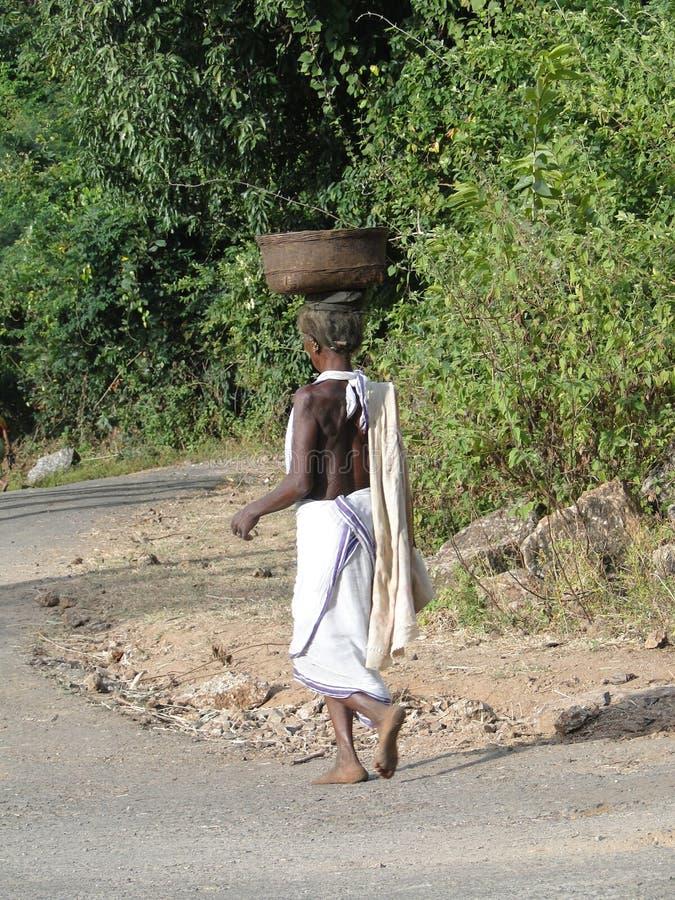 Le donne trasportano le merci sulla loro testa fotografia stock