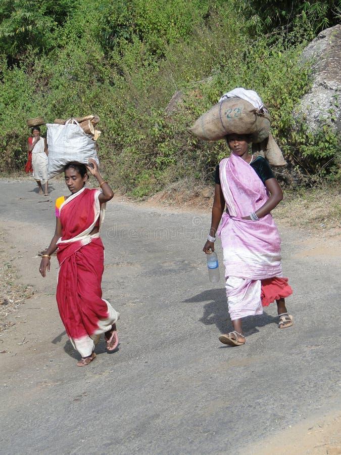 Le donne trasportano le merci sulle loro teste immagini stock