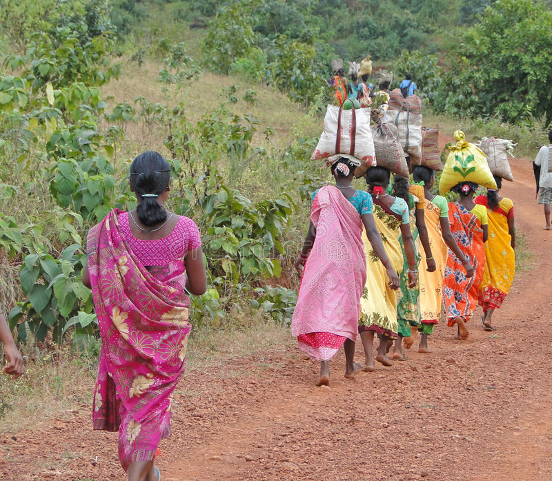 Le donne trasportano le merci sulle loro teste fotografia stock
