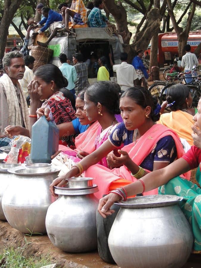 Le donne tribali vendono il liquore a casa fatto dai grandi vasi del metallo fotografie stock