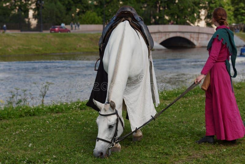 Le donne in vestiti medievali prepara un cavallo per jousting fotografia stock libera da diritti