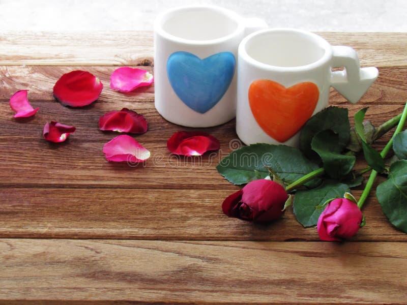 Le doppie tazze bianche come quella rappresenta le coppie sono blu in forma di cuore ed arancio dipinti La parte anteriore ha ros immagine stock