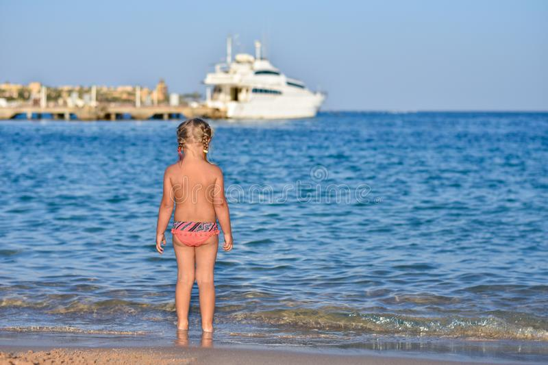 Le dos d'une petite fille dans un maillot de bain sur la plage, un yacht en mer photos stock
