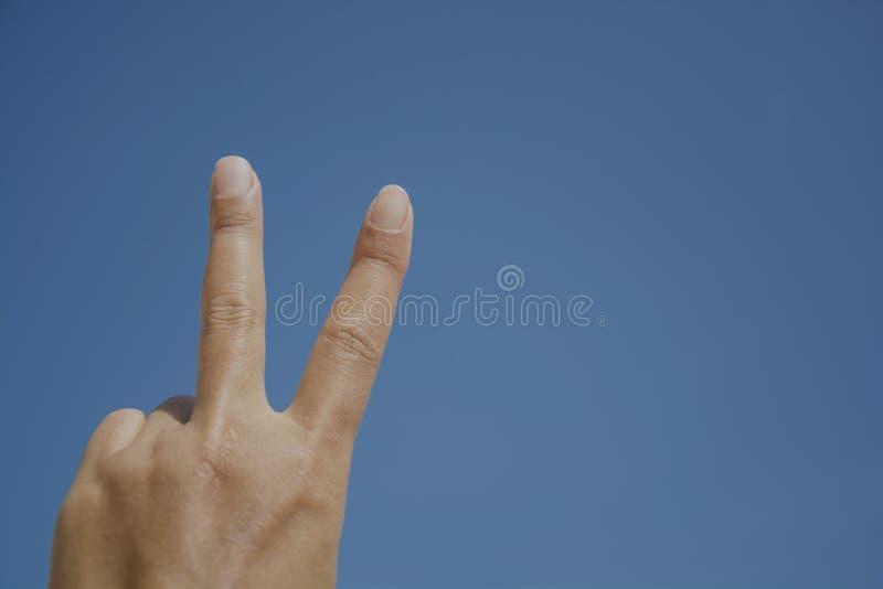 Le dos de l'exposition de main le signe de victoire contre de la main de femme avec le ciel bleu, forme de doigt photo stock