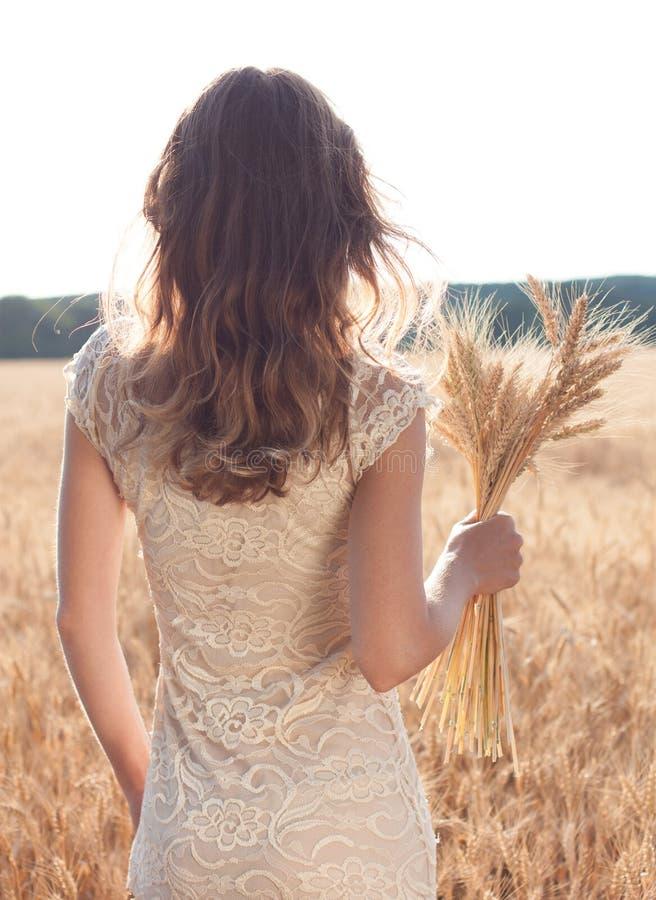 Le dos de la fille dans un domaine de blé avec des oreilles de blé photographie stock