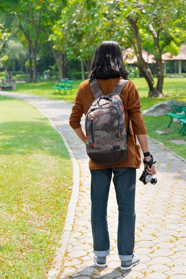 Le dos des hommes qui se promènent et regardent dans le jardin, il porte un sac à dos et tient un appareil photo image stock