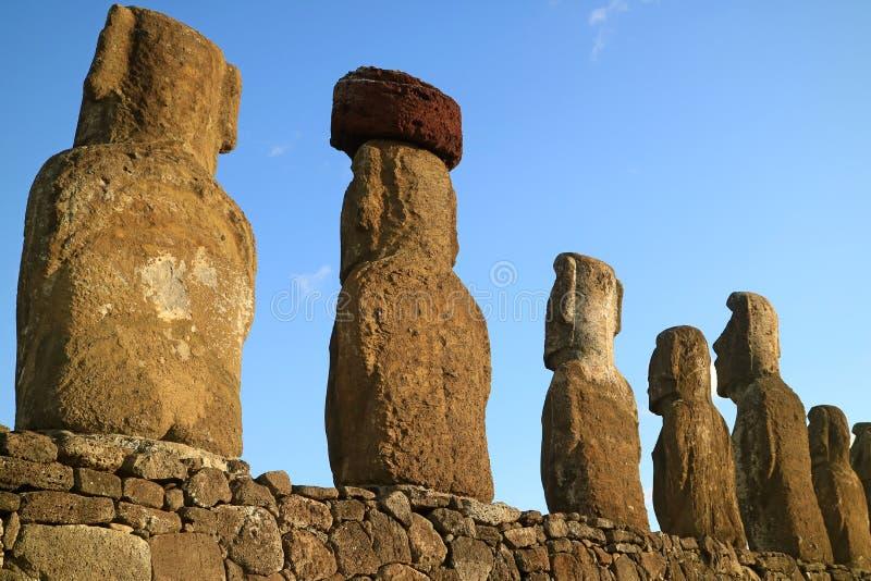 Le dos des statues gigantesques de Moai chez Ahu Tongariki, un avec le noeud supérieur a appelé Pukao fait à partir du Scoria  photos stock