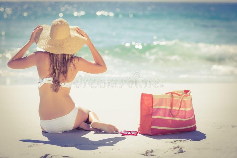 Le dos a tourné la blonde dans le maillot de bain se reposant sur la plage images libres de droits