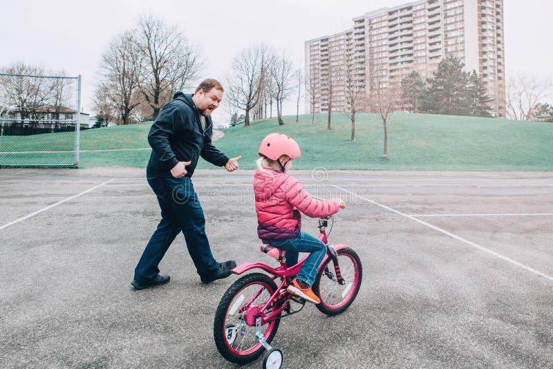 Le dottern f?r flicka f?r upphetsad Caucasian faderutbildning den hj?lpande f?r att rida cykeln fotografering för bildbyråer