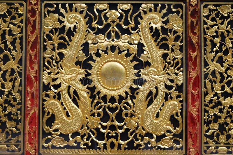 Le dragon d'or conçoit sur le piédestal d'un autel photos stock