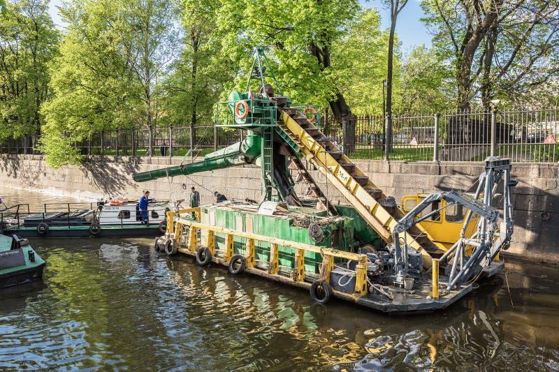 Le dragueur à godets multiples travaille à nettoyer le fond du canal dans Kronstadt des débris inférieurs photographie stock