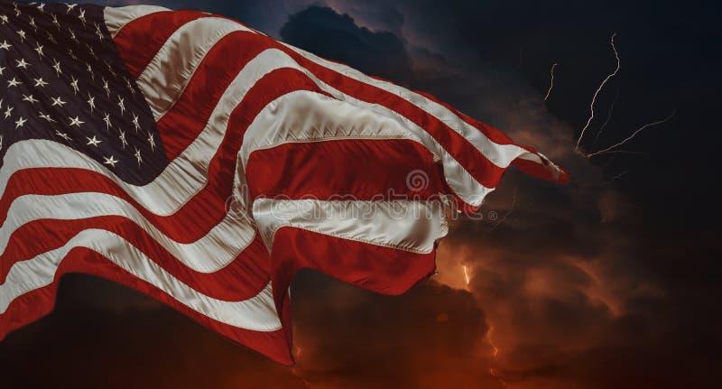 Le drapeau américain ondulant dans l'orage de vent avec les fourchettes multiples de foudre de la foudre percent le ciel nocturne photographie stock libre de droits
