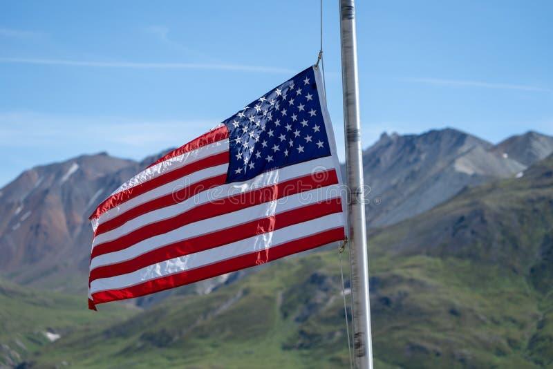 Le drapeau américain vole devant les montagnes de chaîne d'Alaska aux visiteurs d'Eielson centrent en parc national de Denali image libre de droits