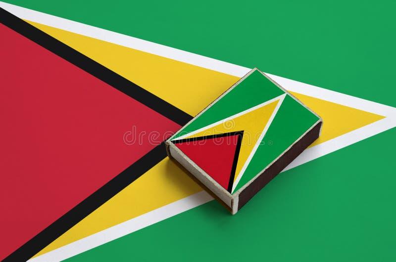 Le drapeau de la Guyane est décrit sur une boîte d'allumettes qui se trouve sur un grand drapeau photographie stock