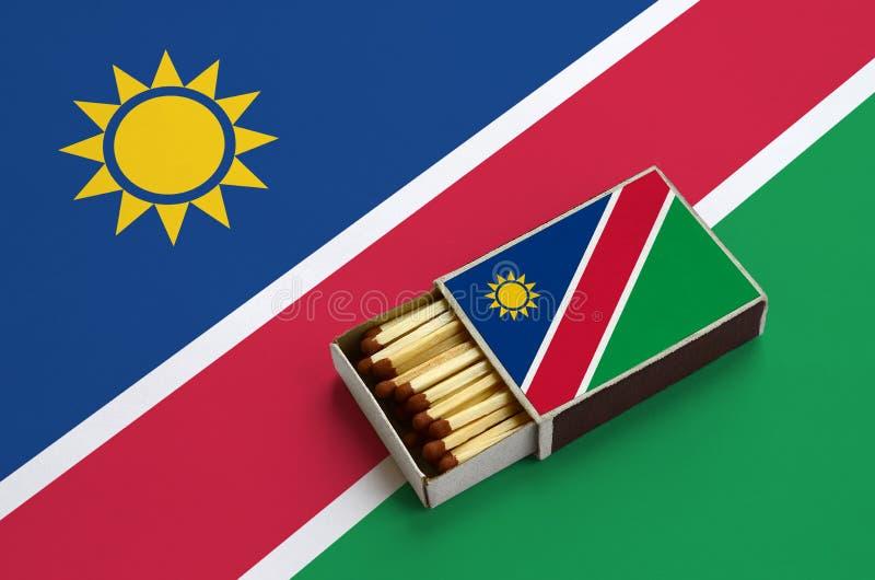 Le drapeau de la Namibie est montré dans une boîte d'allumettes ouverte, qui est remplie de matchs et se trouve sur un grand drap illustration libre de droits