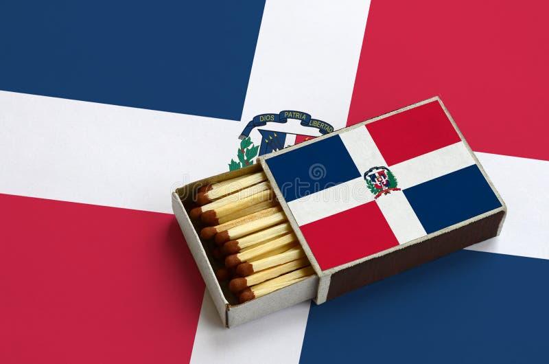 Le drapeau de la République Dominicaine est montré dans une boîte d'allumettes ouverte, qui est remplie de matchs et se trouve su illustration stock