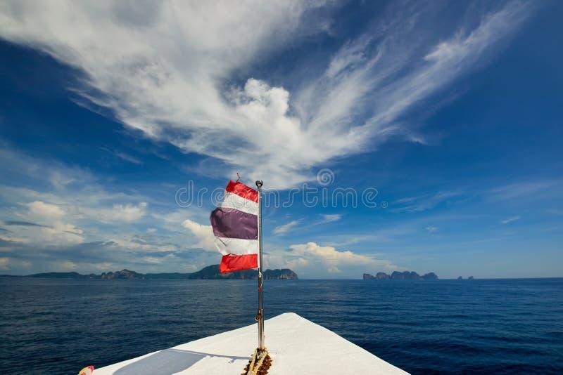 Le drapeau de la Thaïlande avec le bateau navigue à l'île de Koh Phi Phi, Thaïlande image stock