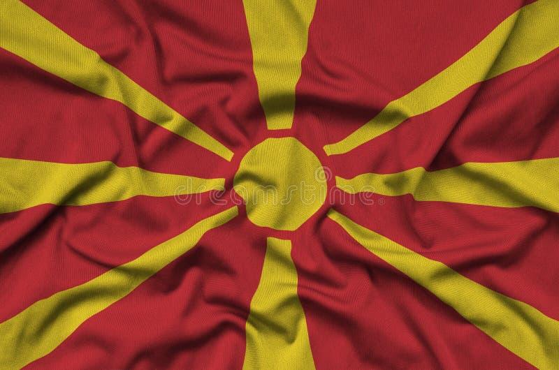 Le drapeau de Macédoine est dépeint sur un tissu de tissu de sports avec beaucoup de plis Bannière d'équipe de sport images libres de droits