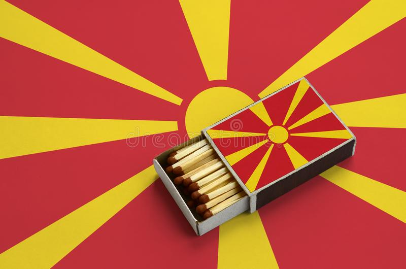 Le drapeau de Macédoine est montré dans une boîte d'allumettes ouverte, qui est remplie de matchs et se trouve sur un grand drape photos libres de droits