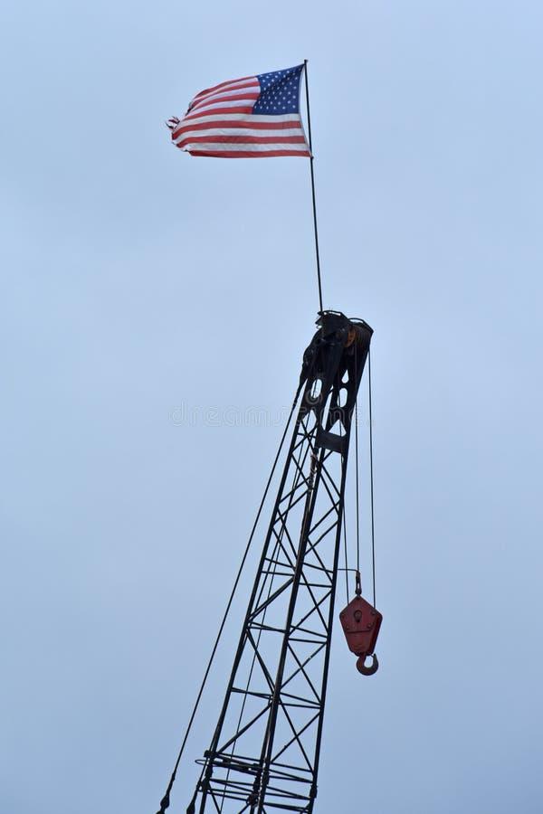 Le drapeau des USA vole en brise placé sur une grue image libre de droits