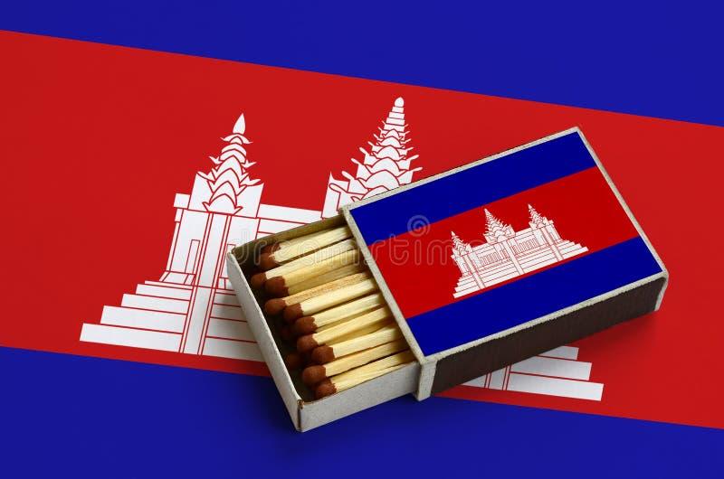 Le drapeau du Cambodge est montré dans une boîte d'allumettes ouverte, qui est remplie de matchs et se trouve sur un grand drapea illustration de vecteur