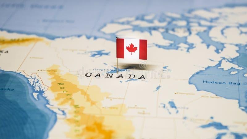 Le drapeau du Canada dans la carte du monde images stock