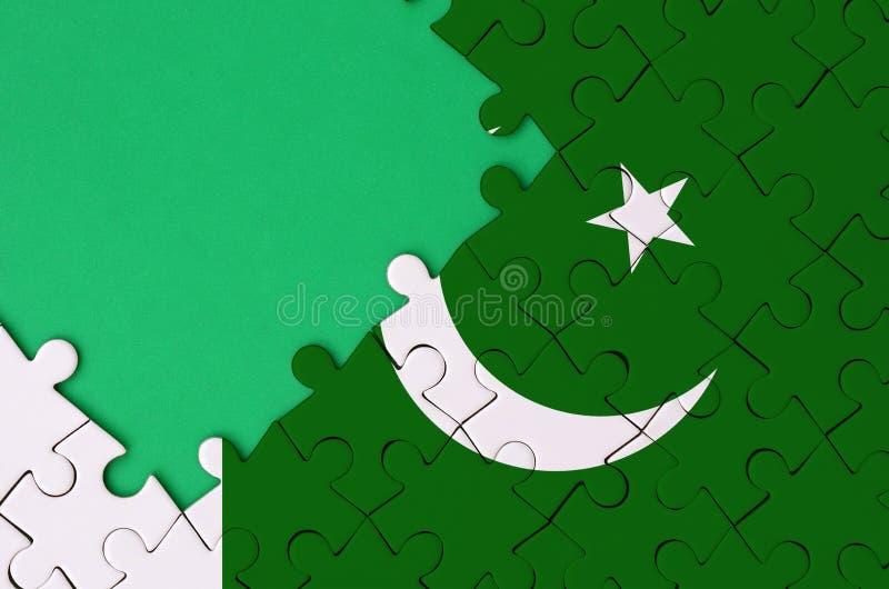 Le drapeau du Pakistan est dépeint sur un puzzle denteux réalisé avec l'espace vert gratuit de copie du côté gauche photos libres de droits