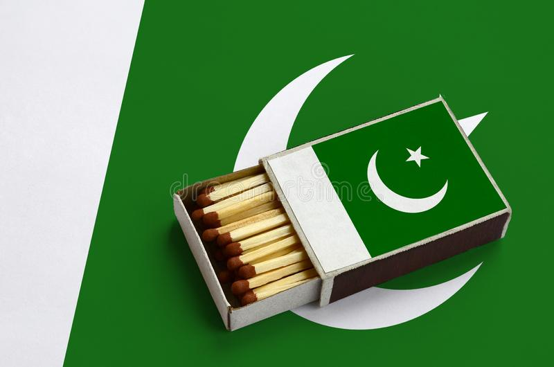 Le drapeau du Pakistan est montré dans une boîte d'allumettes ouverte, qui est remplie de matchs et se trouve sur un grand drapea photographie stock libre de droits