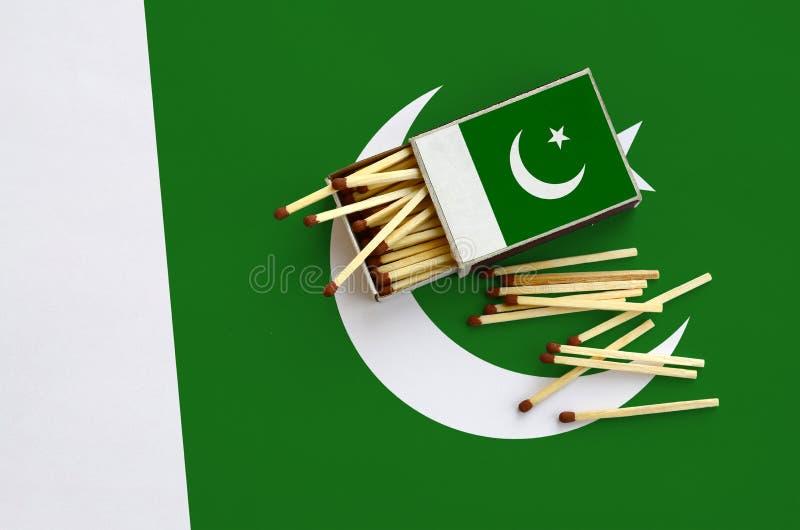 Le drapeau du Pakistan est montré sur une boîte d'allumettes ouverte, de laquelle plusieurs matchs tombent et des mensonges sur u images stock