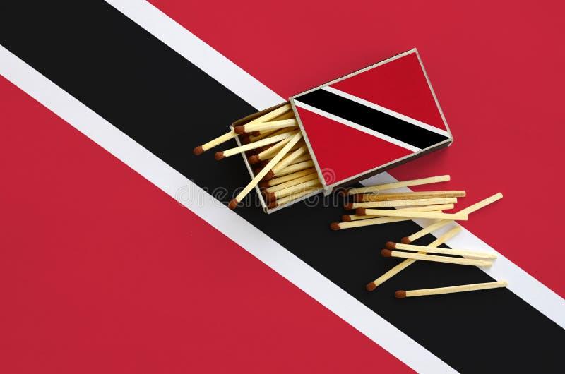 Le drapeau du Trinidad-et-Tobago est montré sur une boîte d'allumettes ouverte, de laquelle plusieurs matchs tombent et des menso illustration de vecteur