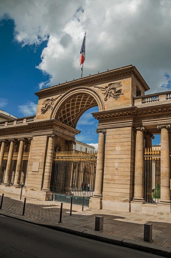 Le drapeau français au-dessus de la voûte en pierre et le fer d'or déclenchent richement décoré dans le jour ensoleillé à Paris photographie stock