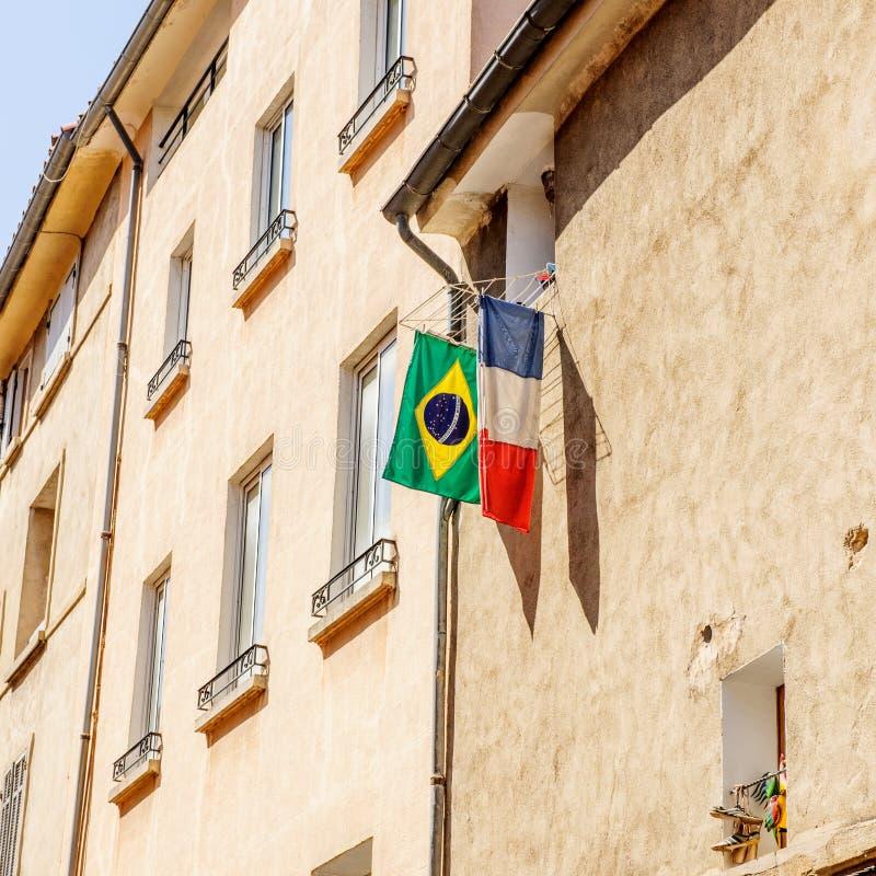 Le drapeau français et brésilien a accroché en dehors de la fenêtre dans la ville photographie stock libre de droits