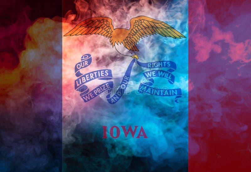 Le drapeau national de l'?tat d'USA Iowa dedans contre une fum?e grise le jour de l'ind?pendance dans diff?rentes couleurs de rou image stock