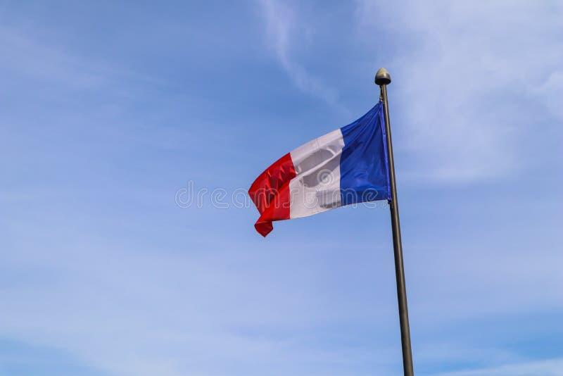 Le drapeau national de la France sur le mât de drapeau se développe dans le vent contre le ciel bleu images libres de droits