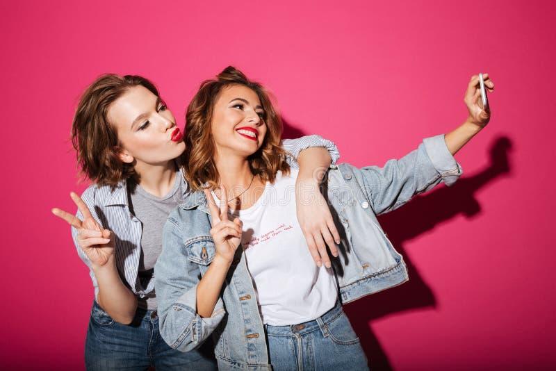 Le due donne allegre fanno il selfie dal telefono immagine stock libera da diritti