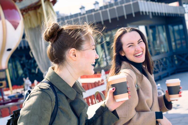 Le due giovani donne felici stanno sorridendo molto e camminata di risata le vie della città un giorno soleggiato, tenenti le taz fotografia stock