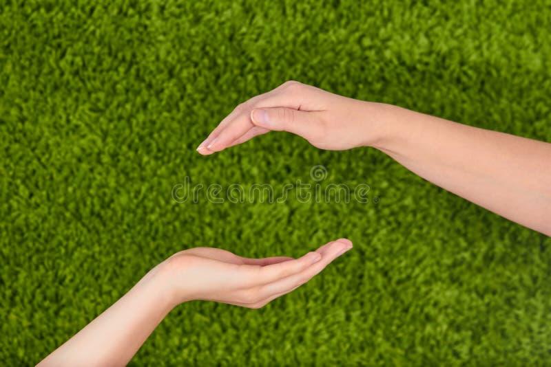 Le due mani aperte della donna che fanno un gesto di protezione fotografie stock libere da diritti