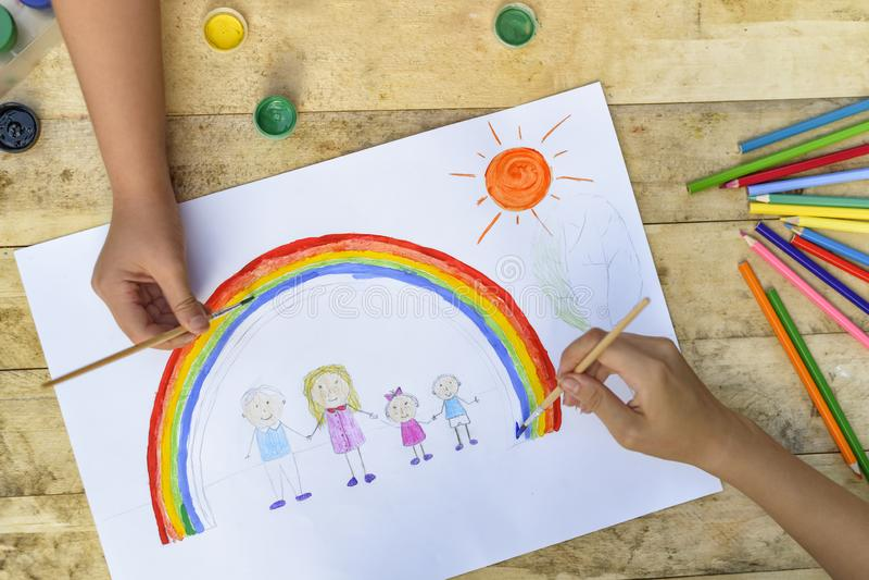 Le due mani dei bambini disegnano un disegno con una spazzola e le pitture top immagine stock