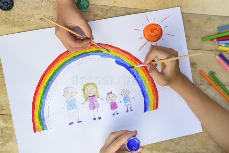 Le due mani dei bambini disegnano un disegno con una spazzola e le pitture top fotografia stock libera da diritti