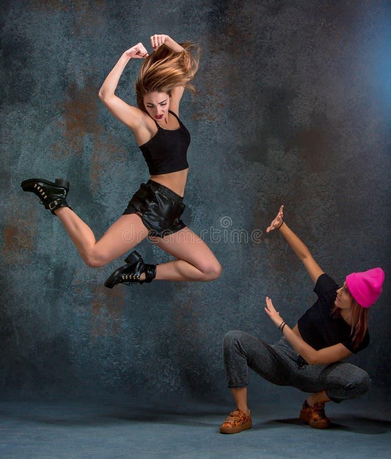 Le due ragazze attraenti che ballano twerk nello studio fotografia stock libera da diritti