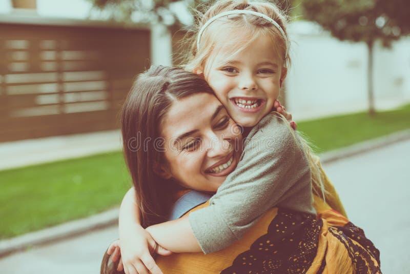 Le elasticità della figlia abbracciano una mamma Bambina felice immagine stock