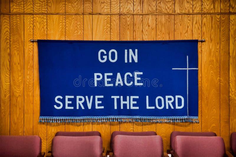 Le ` entrent dans le service de paix le ` de seigneur écrit sur le tissu bleu-foncé accrochant sur le mur derrière les chaises ro images stock
