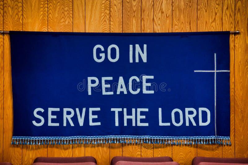 Le ` entrent dans le service de paix le ` de seigneur écrit sur le tissu bleu-foncé accrochant sur le mur derrière les chaises ro image stock