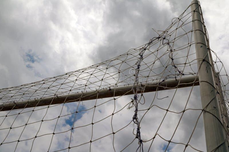 Le but et le filet du football, tirant du dos sur beaucoup opacifient le fond de ciel photo libre de droits
