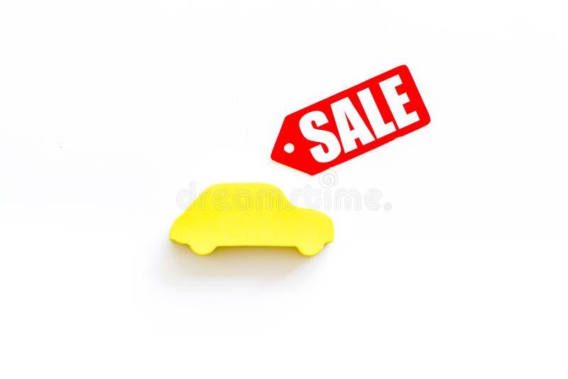 Le etichette e l'automobile di vendita dipendono la vista superiore del fondo bianco fotografia stock
