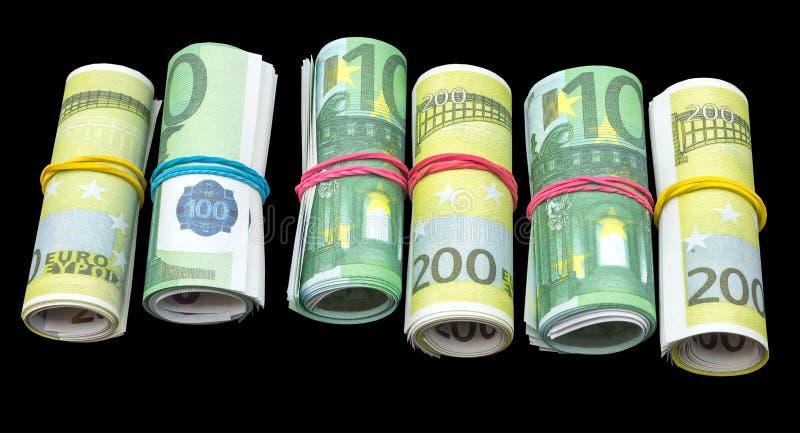 Le euro banconote dei soldi rotolano sul nero immagine stock libera da diritti