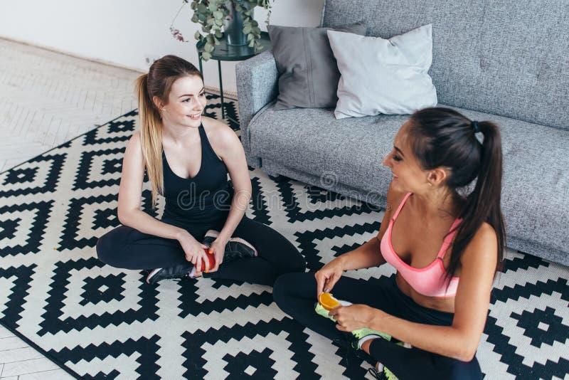 Le färdiga kvinnor som bär sportswearsammanträde på golvet som äter frukter och samtal royaltyfri bild