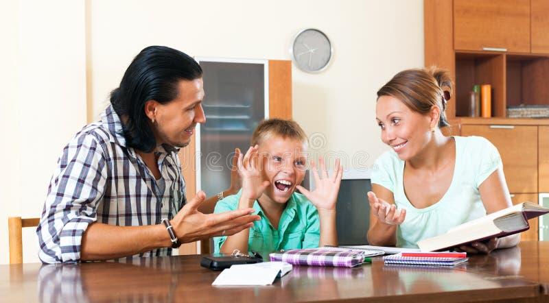Le föräldrar som hjälper med läxa fotografering för bildbyråer