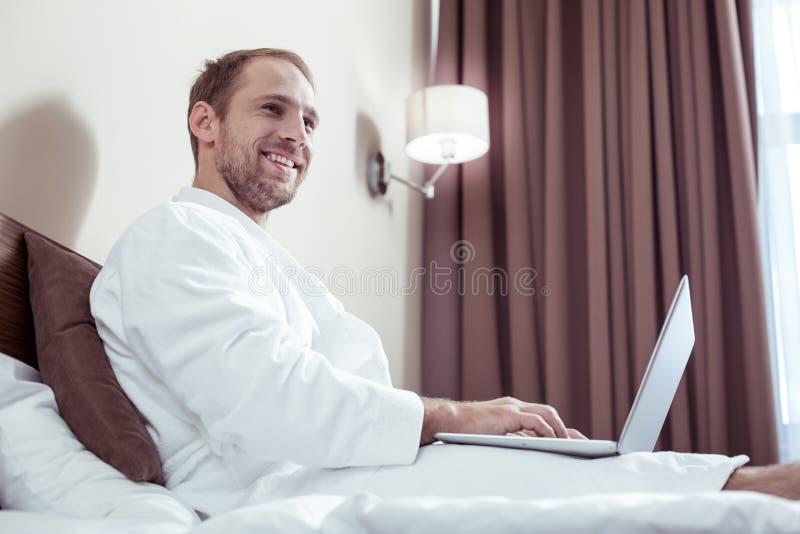 Le för badrockutgifter för angenäm man bärande vit morgon i hotell arkivbilder